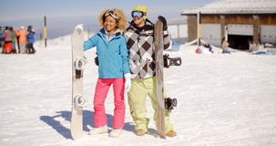 Happy young couple posing with their snowboards Stock Photography