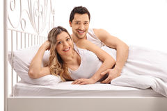 Happy young couple posing together in bed Royalty Free Stock Images