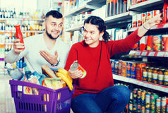 Happy young couple purchasing tinned goods Royalty Free Stock Photography