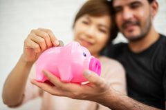 Couple putting coin into Pink Piggy Bank. Happy Young couple putting coin into Pink Piggy Bank. Successful, Achievement concepts royalty free stock images