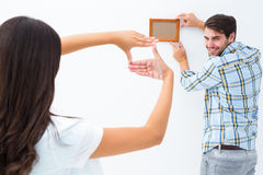 Happy young couple putting up picture frame Royalty Free Stock Photography