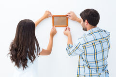 Happy young couple putting up picture frame Royalty Free Stock Photos