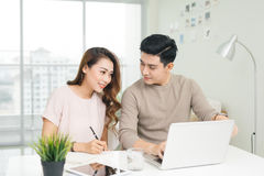 Happy young couple reading and analyzing bills sitting at table. Young couple in casual discussing home economics Stock Photography