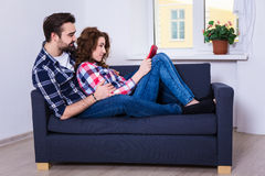 Happy young couple reading book on sofa. In living room Stock Image