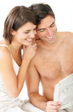 Happy young couple reading newspaper together Stock Photo