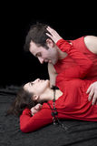 Happy young couple in red against black background Royalty Free Stock Photos