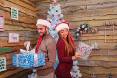 Happy couple in red elf hat, stand backs to each other and holding Christmas gift boxes. Indoors. stock image
