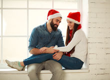 Happy young couple in red Christmas hats sitting on window Royalty Free Stock Photography