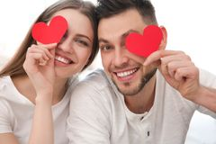 Happy young couple with red paper hearts Royalty Free Stock Photos