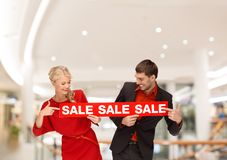 Happy young couple with red shopping bags in mall Stock Photo