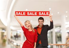 Happy young couple with red shopping bags in mall. Sale, consumerism, advertisement and people concept - happy young couple holding red advertising board in mall Stock Images