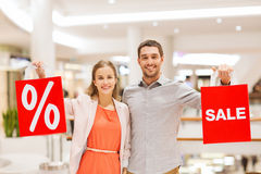Happy young couple with red shopping bags in mall Royalty Free Stock Photography
