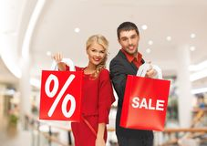 Happy young couple with red shopping bags in mall Royalty Free Stock Images