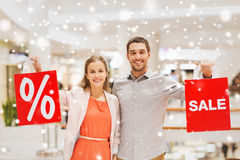 Happy young couple with red shopping bags in mall. Sale, consumerism and people concept - happy young couple with red shopping bags in mall with snow effect Royalty Free Stock Image