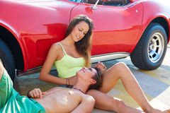 Happy young couple relaxed in a car side sitting Royalty Free Stock Photos