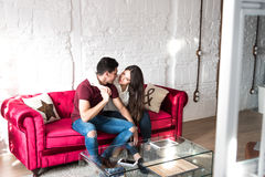 Happy young couple relaxed at home sitting on the couch Royalty Free Stock Photography