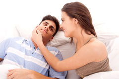 Happy young couple relaxing. Portrait of a young beautiful couple relaxing on the bed royalty free stock photography