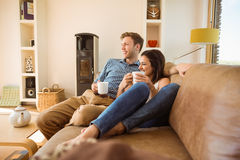 Happy young couple relaxing on the couch Stock Photos
