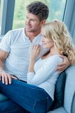 Happy young couple relaxing on a couch at home Royalty Free Stock Images
