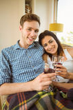 Happy young couple relaxing on the couch with red wine Stock Photo