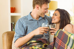 Happy young couple relaxing on the couch with red wine Stock Photos