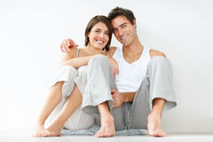 Happy young couple relaxing on the floor Royalty Free Stock Image