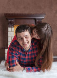 Happy young couple relaxing at home near the fireplace. Hug on a white carpet royalty free stock photos