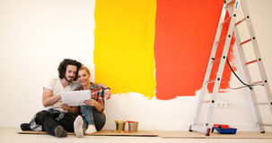 Happy young couple relaxing after painting stock photography