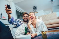 Young couple relaxing and watching TV at home stock photo