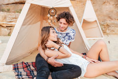 Happy young couple relaxing in wigwam on the beach Stock Images