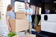 Happy Young Couple Relocating. Portrait of smiling young men handing cardboard box to wife unloading moving van outdoors royalty free stock photos