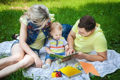Happy family reading book in park. Happy young couple resting in city park, fine couple reading book with his little son, concept happy family Royalty Free Stock Images