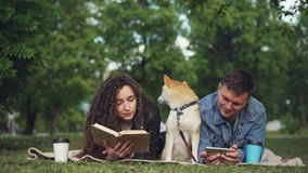 Happy couple is resting in park, man is using smartphone while woman is reading book, their dog is sitting between them. Happy young couple is resting in park stock footage