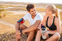 Happy young couple resting together with bottle of water. Outdoors stock image
