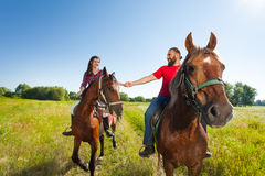 Happy young couple riding bay horses holding hands Stock Photo