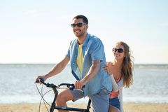 Happy young couple riding bicycle on beach Stock Photo