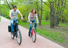 Happy young couple riding bicycles Stock Image