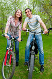 Happy young couple riding bicycles Stock Photos