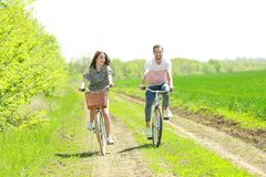 Happy young couple riding bicycles. In countryside Royalty Free Stock Photo