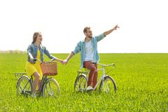 Happy young couple riding bicycles. In green field Stock Images