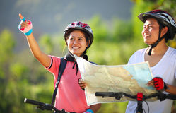 Happy young couple riding a bike Stock Images