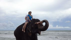 Happy young couple is riding on an elephant with trunk up on the background of a tropical ocean