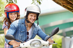 Happy young couple riding a scooter Royalty Free Stock Photo