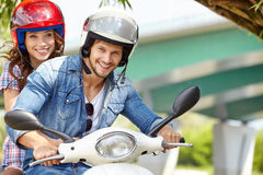 Happy young couple riding a scooter Stock Photo