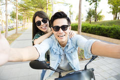 Happy young couple riding  scooter and making selfie photo Royalty Free Stock Images