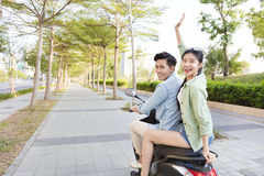 Happy young couple riding  scooter in town Stock Images