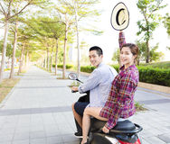 Happy young couple riding  scooter in town Stock Photos