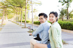 Happy young couple riding  scooter in town Stock Image
