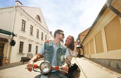 Happy young couple riding scooter in town. Handsome guy and young woman travel. Adventure and vacations concept. Stock Photography
