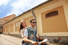 Happy young couple riding scooter in town. Handsome guy and young woman travel. Adventure and vacations concept. Stock Images